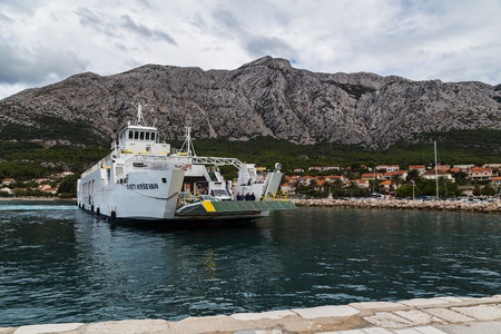 The ramp of the local car ferry begins to open as it approaches Orebic, seen at the foot of the Sveti Ilija Mountain - the highest peak on the rocky Peljesac peninsula in Croatia.