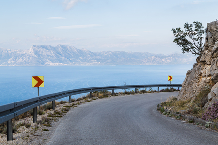 A bend in the steep coastal road at Oskorusno on the northern side of the Peljesac pensinsula in Croatia.  The start of the Biokovo mountain range can be seen in the distance, the second-highest mountain range in Croatia. Stock Photo