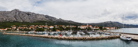 A multiple image panorama of Orebic marina seen from the top of a car ferry as it prepares to depart the mainland across the short channel of water of Korcula Island.