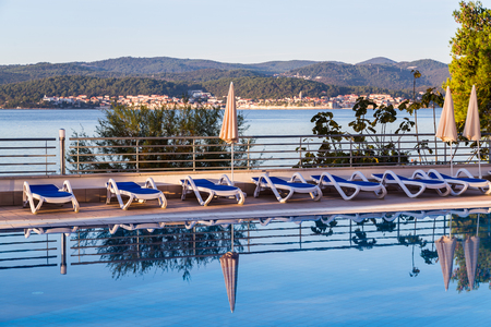 The still water on a hotel swimming pool pictured in front of Korcula old town which shuts out into the Peljesac Channel on its own peninsula.