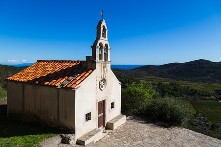 A tiny church on the edge of the rural village of Smokvica on Korcula Island, pictured in front of the vineyards in the valley below and under a blue sky. Stock Photo