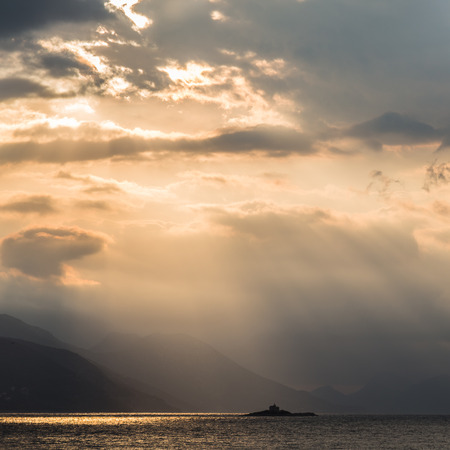 Rays of sunlight peak through the low cloud and light up parts of the Peljesac peninsula and the Peljesac Channel beneath. Stock Photo