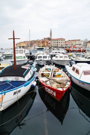 Colourful boats full of fishing equipment fill the foreground as they are moored in Rovinj harbour.