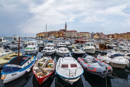 Boats bob up and down on the water as they are moored to the promenade of Rovinj harbour.