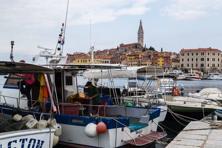 Fishermen on the back of their boat sorting their nets for the next morning - seen in Rovinj in September 2019. 写真素材