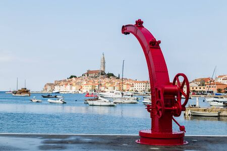 An old red boat crane frames the old town of Rovinj on a hilly peninsula, surrounded by the Adriatic Sea in Croatia. 写真素材