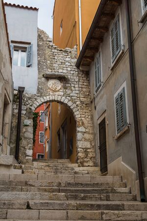 Looking up some steps in a narrow street of Rovinj, Croatia, towards a limestone built arch.
