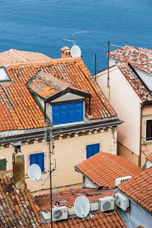 Looking down on a couple of rooftops in Rovinjs old town as the modern satellite dishes contrast with the old terracotta roof tiles.