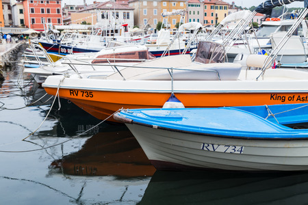 Differing colours and sizes of fishing boats moored to the quayside in Rovinj harbour captured in September 2019.