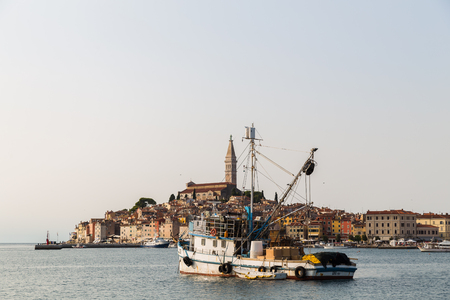 A fishing trawler is moored in part of the harbour of Rovinj with the old town seen in the background.
