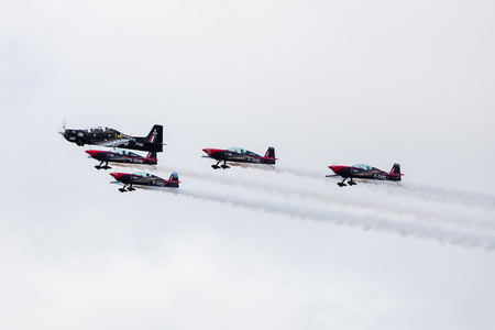 RAF Tucano and The Blades aerobatic display team in close formation at the Southport airshow (in September 2019) to celebrate the centenary year of the RAF Benevolent Fund. 写真素材 - 132420262