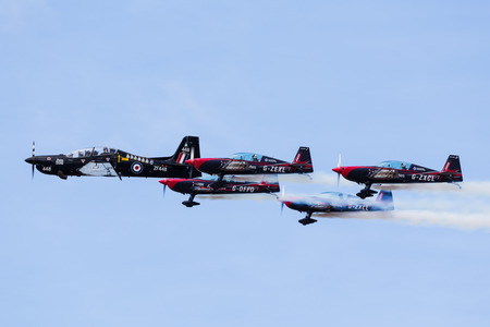RAF Tucano and The Blades aerobatic display team in close formation at the Southport airshow (in September 2019) to celebrate the centenary year of the RAF Benevolent Fund. 報道画像