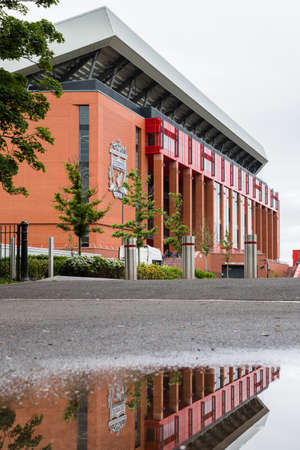 Gigantic new Main stand of Anfield stadium (home of Liverpool FC) seen in England in June 2020 reflecting in a puddle of water.