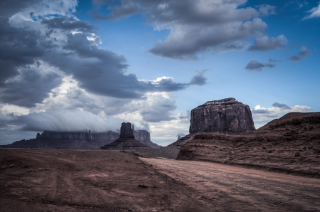 Monument valley road with big thunder cloud in background  Sandstone formation in Monument Valley during sunset