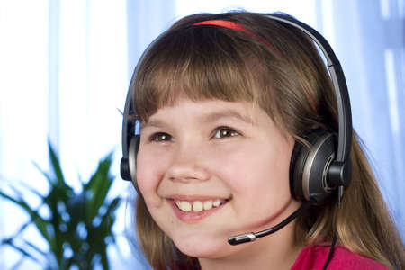 a child with a headset smiling and looking Stock Photo