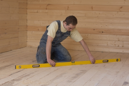 Carpenter checks the accuracy of the horizontal position of the wooden floor