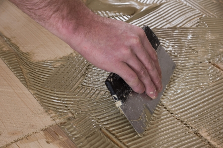 Work to apply the adhesive on the plywood for laying parquet. Stock Photo