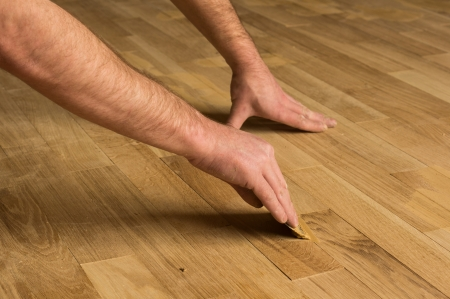 The employee puttied wooden floor inside the house.