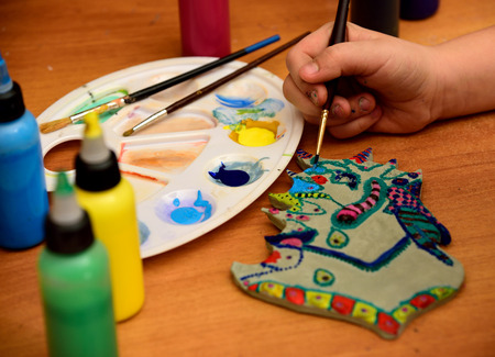 Girl paints a clay toy on the background palette with paints and bubbles.