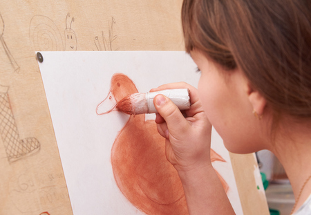 Girl draws sanguine duck burgundy color on an easel Stock Photo
