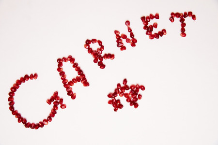 Caption garnet grains of pomegranate laid on a white background.