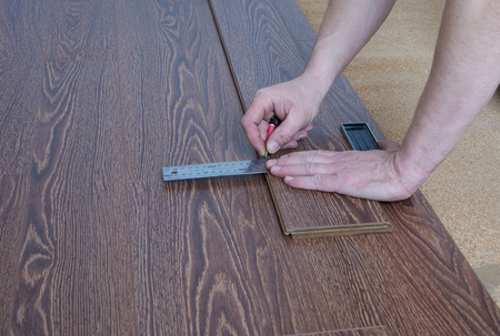Worker produces markup laminate flooring oak color chocolate Stock Photo