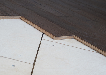 Flooring made of solid oak brown lying on birch plywood.