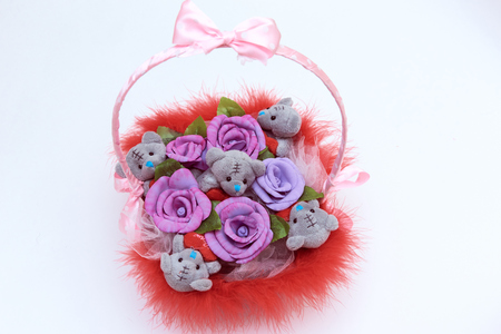Basket with pink handle, filled with teddy  bears and flowers