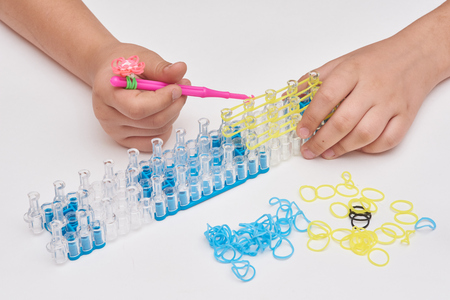 The girl makes a bracelet out of rubber rings with the help of the machine and the hook.