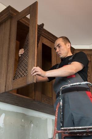 Carpenter sets the grate in the door hanging cupboard.