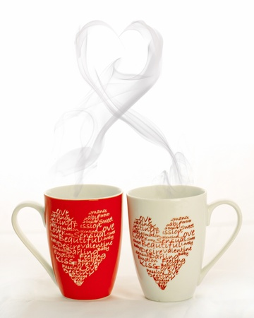 Coffee cups with hearts on a white background with smoke that has shape of a heart photo