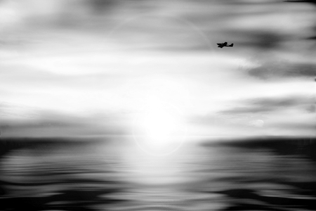 horizon over water: Unsharp landscape with aircraft black white