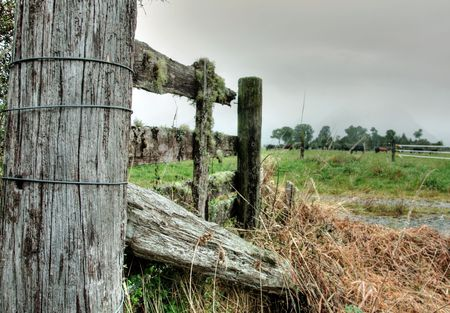 A broken wooden fence on farmland