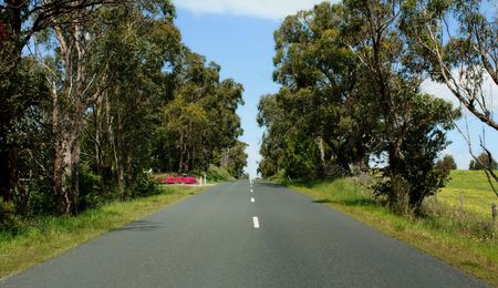 a country road with blue cloudy sky