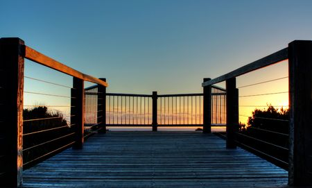 Wooden deck on coastline of Great Ocean Road, Australia during sunset