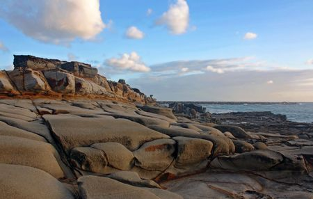 Rocky lookout at Yamba beach against a cloudy sky