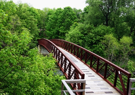 a woodend bridge leading into a forest Stock Photo