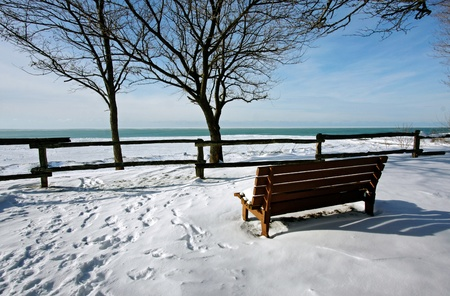 a winter scene of a snow-covered bench overlooking the lake photo