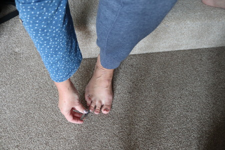 adult using a pedicure set on toe nails Standard-Bild