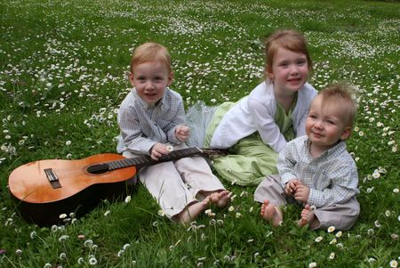 Three siblings, patch of dasies and a guitar