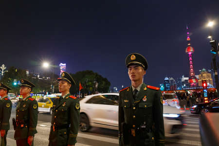 China Soldiers standing in attention position in front of The Bund, Shanghai China with Oriental Pearl TV Tower as the backdrop