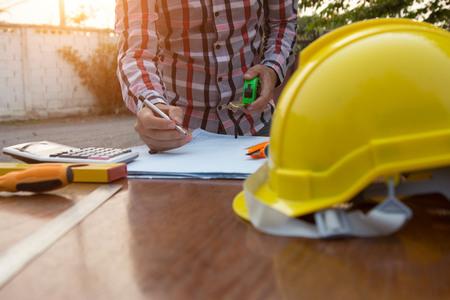 Ingenieur en architect schaven en bespreken op bouwplaats met blauwdruk