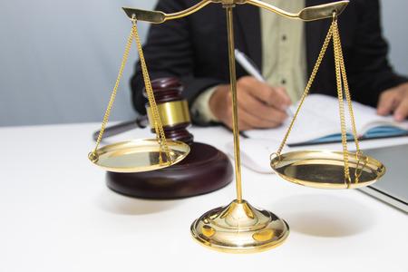 Abogado de negocios escribiendo impuestos en el lugar de trabajo de escritorio de oficina con libros y documentos. Foto de archivo