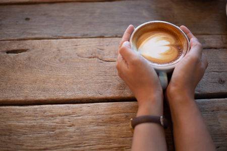 Hand Women put a Latte arts coffe hot coffee on wooden table.barista art concept.