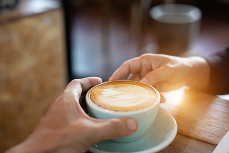 Hand Women and man put a Latte arts coffe hot coffee on wooden table.barista love art concept.