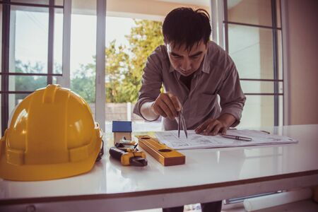 Engineer man drawings blueprint at Construction Site.Home Project to Offer Management