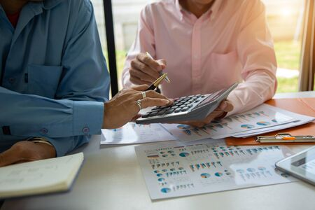 Team businessman using calculator and holding pen on tax paper in office.Accounting concept. Stock Photo