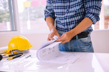 architect man reading with blueprint to build houses. After agreeing the employment price the cost of construction and repair real estate