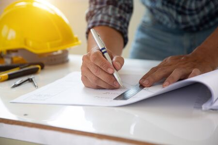 architect man handwriting with blueprint to build houses. After agreeing the employment price the cost of construction and repair real estate