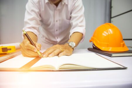 Working process startup. Engineer working at the wood table . Modern notebook on table. Pen holding hand.